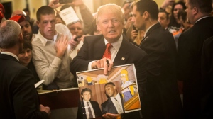 "FILE - In this Jan. 29, 2016, file photo, Republican presidential candidate Donald Trump holds depictions of himself on, ""The Simpsons"" and a photo with boxer Mike Tyson, given to him by an attendee during a campaign stop at the Radisson Hotel in Nashua, N.H. ""The Simpsons"" released a short online clip on April 26, 2017, mocking President Donald Trump ahead of his 100th day in office. (AP Photo/John Minchillo, File)"