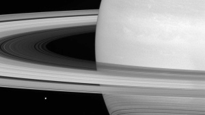 This undated photo made available by NASA shows one of Saturn's moons, Mimas, dwarfed by the planet's rings. (NASA/JPL-Caltech/Space Science Institute via AP)