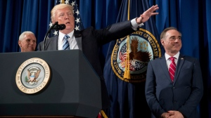 """President Donald Trump, accompanied by Vice President Mike Pence, left, and Veterans Affairs Secretary David Shulkin, right, speaks before signing an Executive Order on """"Improving Accountability and Whistleblower Protection"""" at the Department of Veterans Affairs, Thursday, April 27, 2017, in Washington. (AP Photo/Andrew Harnik)"""
