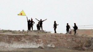 In this Monday, June 15, 2015 file photo taken from the Turkish side of the border between Turkey and Syria, in Akcakale, southeastern Turkey, Kurdish fighters with the Kurdish People's Protection Units, or YPG, wave their yellow triangular flag in the outskirts of Tal Abyad, Syria. As Kurdish rebels in northern Syrian rack up wins against the Islamic State group, Turkey's press is once again abuzz with talk of plans for a long-debated intervention aimed at pushing the radical religious group back from its border, and outflanking any Kurdish attempt at creating a state along Turkey's southern frontier. (AP Photo/Lefteris Pitarakis, file)