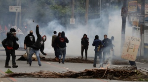 A demonstrator throws a stone amid clouds of tear gas during clashes with the police next to Sao Paulo's University during a general strike in Sao Paulo, Brazil, Friday, April 28, 2017. Buses, trains and metros have been halted across much of Brazil as a general strike kicks off. Transportation unions and several other groups are protesting changes to labor laws and the pension system being considered by Congress. (AP Photo/Andre Penner)