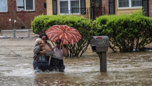 Nautica Jackson, left, and Aniya Ruffin walk through floodwaters with their dog as water threatened to enter their home in Raleigh, N.C. Tuesday, April 25, 2017. (Travis Long/The News & Observer via AP)