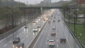 Vehicles drive along the Don Valley Parkway as heavy rains swell the adjacent Don River Friday May 5, 2017.