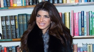 """In this Feb. 16, 2016 file photo, TV personality Teresa Giudice appears at a book signing for her new book """"Turning the Tables: From Housewife to Inmate and Back Again"""" in Huntington, N.Y.  (Photo by Scott Roth/Invision/AP, File)"""