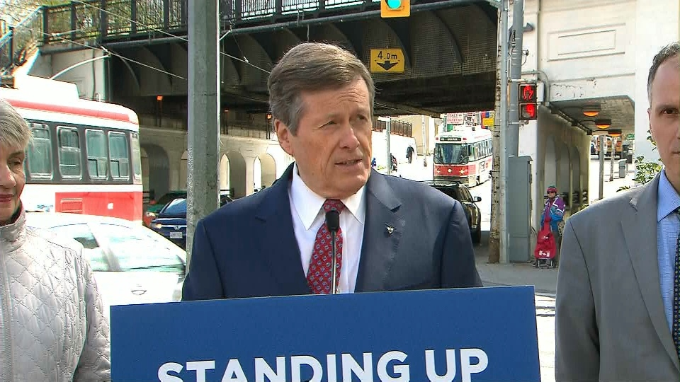 Mayor John Tory speaks with reporters near the intersection of Gerrard Street and Carlaw Avenue on Tuesday.
