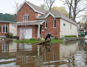 A man removes debris from the floodwaters surrounding his house in Deux-Montagnes, Que., on Wednesday, May 10, 2017. THE CANADIAN PRESS/Ryan Remiorz