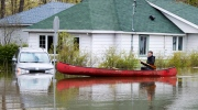 A resident paddles through the flooded streets Tuesday, May 9, 2017 in Deux-Montagnes, Quebec. THE CANADIAN PRESS/Ryan Remiorz