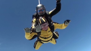 In this grab taken from video, Verdun Hayes gestures prior to tandem skydiving, in Devon, England, Sunday, May 14, 2017. A 101-year-old D-Day veteran has broken the world record for the oldest tandem skydiver. Hayes, a great-grandfather, jumped out of a plane from 15-thousand feet in Devon, UK, on Sunday accompanied by four generations of his family. (Skydive.buzz via AP)