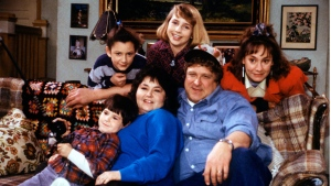 """In this undated image released by ABC, shows the cast members of """"Roseanne,"""" Michael Fishman as DJ Conner, seated from left, Roseanne Barr as Roseanne Barr, John Goodman as Dan Conner, and second row from left, Sara Gilbert as Darlene Conner, Alicia Goranson as Becky Conner and Laurie Metcalf as Jackie Harris. (Dan Watson/ABC via AP)"""