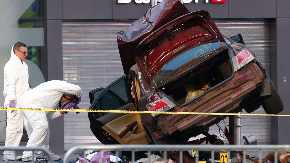 Investigators photograph evidence at the scene of a crash that killed one person and injured almost two dozen others in Times Square, Thursday, May 18, 2017, in New York. Police say a man steered his car onto a sidewalk running through the heart of Times Square mowing down pedestrians for three blocks. He then emerged from his wrecked vehicle wild-eyed and waving his arms before he was subdued by police and bystanders. (AP Photo/Kathy Willens)