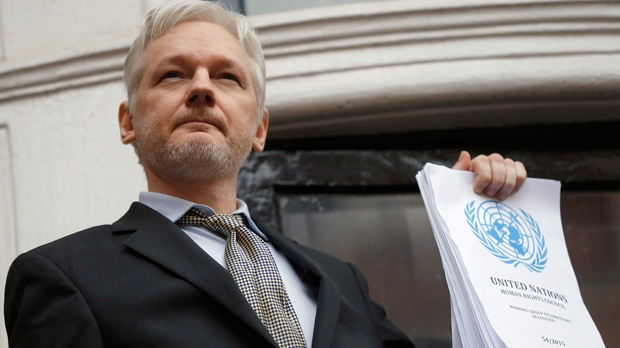 This is a Friday, Feb. 5, 2016 file photo of WikiLeaks founder Julian Assange holds a U.N. report as he speaks on the balcony of the Ecuadorian Embassy in London.  A U.N. panel is sticking by its opinion that WikiLeaks founder Julian Assange is a victim of arbitrary detention, rejecting a request by Britain to review the case. The Working Group on Arbitrary Detention found that Britain had not presented enough new information to merit a new examination. The panel made the decision at a meeting last week, the U.N. human rights office said Wednesday, Nov. 30, 2016. (AP Photo/Frank Augstein, File)
