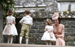 Kate, the Duchess of Cambridge, right, smiles at her daughter Princess Charlotte, after the wedding of her sister Pippa Middleton to James Matthews, at St Mark's Church in Englefield, England Saturday, May 20, 2017. Middleton, the sister of Kate, Duchess of Cambridge married hedge fund manager James Matthews in a ceremony Saturday where her niece and nephew Prince George and Princess Charlotte was in the wedding party, along with sister Kate and princes Harry and William. (Justin Tallis/Pool Photo via AP)
