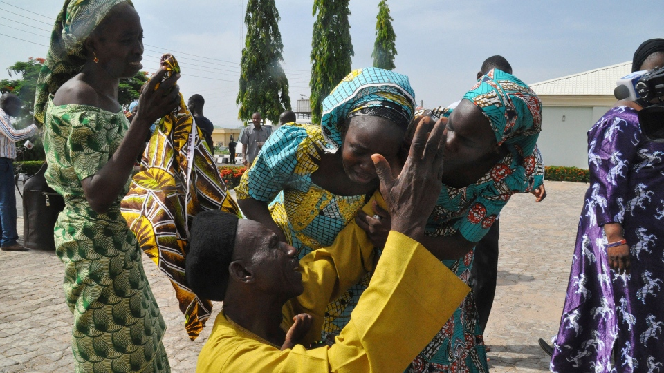 Family members celebrate as they embrace a relative, one of the released kidnapped schoolgirls, in Abuja, Nigeria, Saturday, May 20, 2017. (AP Photo/Olamikan Gbemiga)