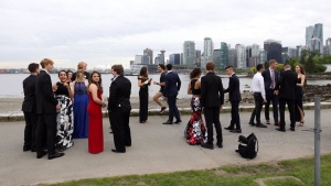 Justin Trudeau runs past a group of students taking prom pictures in Vancouver Friday May 19, 2017. (@AdamScotti /Twitter)