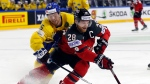 Sweden's Oscar Lindberg, left, challenges for the puck with Canada's Claude Giroux during the Ice Hockey World Championships final match between Canada and Sweden in the LANXESS arena in Cologne, Germany, Sunday, May 21, 2017. (AP Photo/Petr David Josek)