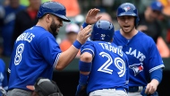 Toronto Blue Jays' Devon Travis, center, is congratulated by Kendrys Morales, left, and Justin Smoak after hitting a three-run home run, scoring them all, against the Baltimore Orioles in the first inning of a baseball game, Sunday, May 21, 2017, in Baltimore. (AP Photo/Gail Burton)