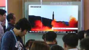 People watch a TV news program showing a file image of a missile launch by North Korea, at the Seoul Railway Station in Seoul, South Korea, Sunday, May 21, 2017. (AP Photo/Ahn Young-joon)