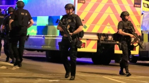 Armed police respond after reports of an explosion at Manchester Arena during an Ariana Grande concert in Manchester, England, Monday, May 22, 2017. (Peter Byrne/PA via AP)