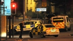 Armed police block a road near to the Manchester Arena in central Manchester, England, Tuesday, May 23, 2017. An explosion struck an Ariana Grande concert in northern England late Monday, killing over a dozen people and injuring dozens in what police say they are treating as a terrorist attack. (AP Photo/Rui Vieira)