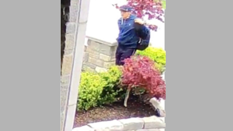 A man with a backpack makes his way around the side of a home on Gorman Avenue in Vaughan in this surveillance image from Monday May 22, 2017. (debra.dibenedetto /Facebook)