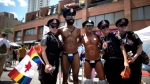 Revellers pose for a photo with police officers at the annual Pride Parade in Toronto on Sunday, July 3, 2016. (Mark Blinch/Canadian Press)