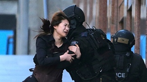 FILE - In this Dec. 15, 2014, file photo, Jieun Bae runs to armed tactical response police officers for safety after she escaped from a cafe under siege at Martin Place in the central business district of Sydney, Australia. Police responding to the deadly hostage crisis in a Sydney cafe underestimated the gunman's threat and should have stormed the building earlier, rather than waiting to act until the gunman had killed a captive, a coroner said on Wednesday, May 24, 2017. (AP Photo/Rob Griffith, File)