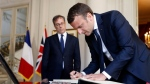 French President Emmanuel Macron meets with British ambassador to France Edward Llewellyn, left, while signing the book of condolences at the British embassy in Paris, France, Tuesday, May 23, 2017. An apparent suicide bomber attacked an Ariana Grande concert as it ended Monday night, killing over a dozen of people among a panicked crowd of young concertgoers. (Etienne Laurent/Pool Photo via AP)