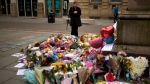 A woman stands next to flowers offered for the victims of a suicide attack at a concert by Ariana Grande that killed more than 20 people Monday night in central Manchester, Britain, Wednesday, May 24 2017. (AP Photo/Emilio Morenatti)