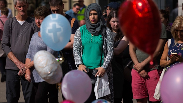 People stand next to flowers in a square in central Manchester, Britain, Wednesday, May 24, 2017, after the suicide attack at an Ariana Grande concert that left more than 20 people dead and many more injured, as it ended on Monday night at the Manchester Arena. (AP Photo/Emilio Morenatti)