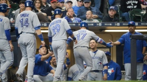 Toronto Blue Jays' Ryan Goins is congratulated after hitting a grand slam during the sixth inning of a baseball game against the Milwaukee Brewers Wednesday, May 24, 2017, in Milwaukee. (AP Photo/Morry Gash)