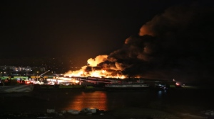 Flames are seen billowing from a six-alarm fire at a Polson Pier recycling facility early Saturday morning. (Deanna Ford)
