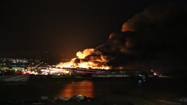 Flames are seen billowing from a six-alarm fire at a Polson Pier recycling facility early Thursday morning. (Deanna Ford)