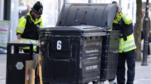 Police officers inspect litter bins in central Manchester, Britain, Thursday May 25 2017. Police are searching a new site in Manchester suspected of links to Monday's bombing at a pop concert. (AP Photo/Rui Vieira)