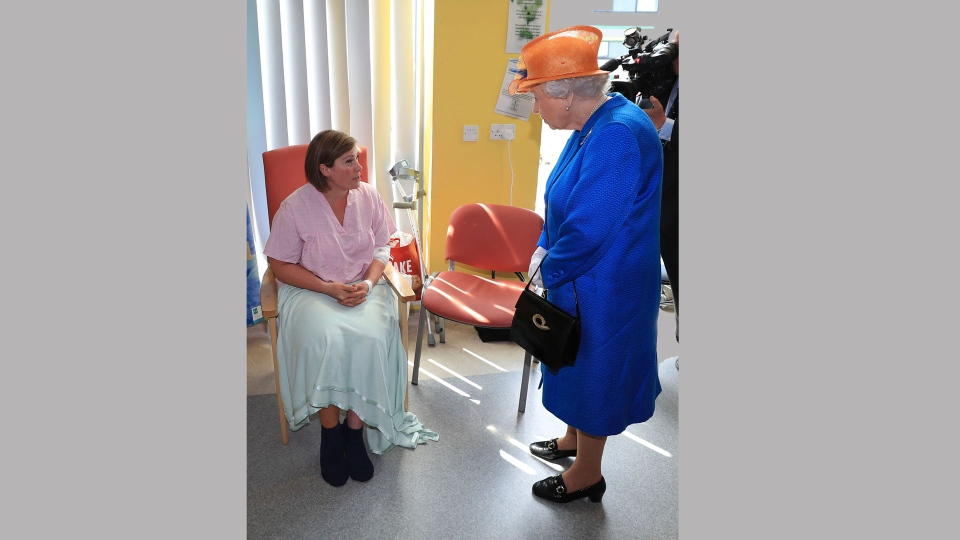 Britain's Queen Elizabeth II, right, speaks to Ruth Murrell, who was injured and whose daughter, Emily, 12, was also injured in Monday's explosion during the Queen's visit to the Royal Manchester Children's Hospital in Manchester England, to meet victims of the terror attack in the city earlier this week and to thank members of staff who treated them Thursday May 25, 2017. (Peter Byrne/Pool via AP)