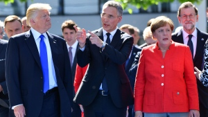 U.S. President Donald Trump, left, NATO Secretary General Jens Stoltenberg and German Chancellor Angela Merkel walk through NATO headquarters at the NATO summit in Brussels on Thursday, May 25, 2017. US President Donald Trump and other NATO heads of state and government on Thursday will inaugurate the new headquarters as well as participating in an official working dinner. (AP Photo/Geert Vanden Wijngaert)