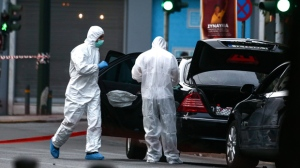 Greek police experts search for evidence at the scene of an explosion site in Athens, on Thursday, May 25, 2017.An explosion inside a car in Greece's capital wounded former Prime Minister Lucas Papademos on Thursday, police said. His injuries were not considered to be life-threatening. (AP Photo/Yorgos Karahalis)