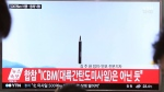 """People watch a TV news program showing a file image of a missile launch conducted by North Korea, at the Seoul Railway Station in Seoul, South Korea, Sunday, May 21, 2017. North Korea on Sunday fired a midrange ballistic missile, U.S. and South Korean officials said, in the latest weapons test for a country speeding up its development of nuclear weapons and missiles. The letters read: """"It does not seem to be an ICBM missile."""" (AP Photo/Ahn Young-joon)"""
