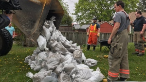 Firefighters in Bowmanville work to place sandbags around homes to hold back floodwaters Friday May 26, 2017. (Tracy Tong /CTV Toronto)