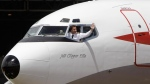 Hollywood actor John Travolta waves from the cockpit of his 707 plane on his arrival in Sydney, Australia, to participate in the 90-year anniversary of Qantas Saturday, Nov. 6, 2010. (AP Photo/Rick Rycroft)