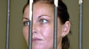 In this Wednesay, Aug. 3, 2005, file photo, convicted drug smuggler Schapelle Corby stands behind the bars at court's prison before her appeal trial in Denpasar's court, Bali, Indonesia. The Australian beauty therapist was sentenced to 20 years in jail in May after 4.1 kilograms of marijuana was found in her bag at the Denpasar airport. During her jail time, Corby has riveted Australia for more than a decade, the everyday Aussie beach girl who somehow sparked diplomatic rows, furious protests and a media bonanza on par with America's O.J. Simpson trial. Next week, after an exhaustively chronicled stint in a Balinese prison for smuggling marijuana to the Indonesian island, Corby is expected to return to Australia. (AP Photo/Firdia Lisnawati, File)