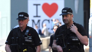 Armed police patrol the streets in central Manchester, England Thursday May 25, 2017. British police arrested two more people Thursday and searched a new site in Manchester suspected of links to Monday's concert bombing that left more than 20 people dead. (AP Photo/Rui Vieira)