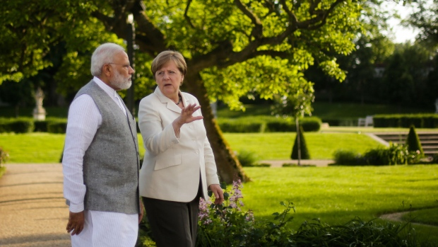 German Chancellor Angela Merkel, centre and Indian Prime Minister Narendra Modi, walk through the garden of the government guest house Meseberg Palace, during a meeting in Meseberg, about 70 kilometers (43 miles) north on Berlin, Monday, May 29, 2017. (AP Photo/Markus Schreiber)