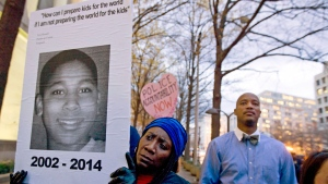 In this Dec. 1, 2014, file photo, Tomiko Shine, left, holds a sign with a photo of Tamir Rice, a boy fatally shot by a Cleveland police officer, while protesting a grand jury's decision in Ferguson, Mo., not to indict police officer Darren Wilson in the shooting death of Michael Brown, during a demonstration in Washington.  (AP Photo/Jose Luis Magana, File)