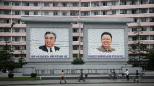North Koreans are dwarfed against giant portraits of the late North Korean leaders Kim Il Sung and Kim Jong Il as they walk past an apartment building in Wonsan, North Korea, on June 22, 2016. (AP / Wong Maye-E)