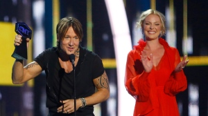 """Keith Urban accepts the award for male video of the year for """"Blue Ain't Your Color"""" at the CMT Music Awards at Music City Center on Wednesday, June 7, 2017, in Nashville, Tenn. Looking on in background right is presenter Katherine Heigl. (Photo by Wade Payne/Invision/AP)"""