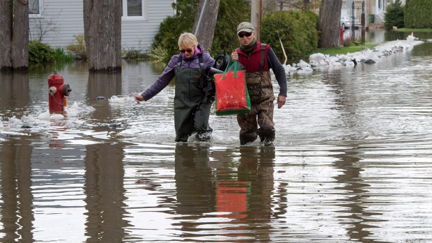 Residents make their way through the flooded streets of Deux-Montagnes, Que., on Wednesday, May 10, 2017. THE CANADIAN PRESS/Ryan Remiorz