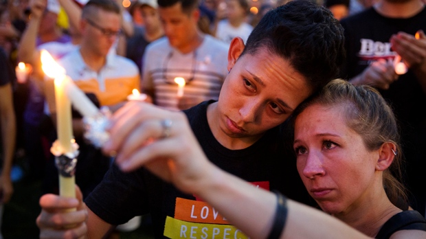 FILE - In this June 13, 2016 file photo, Jennifer, right, and Mary Ware light candles during a vigil downtown for the victims of a mass shooting at the Pulse nightclub in Orlando, Fla. (AP Photo/David Goldman, File)