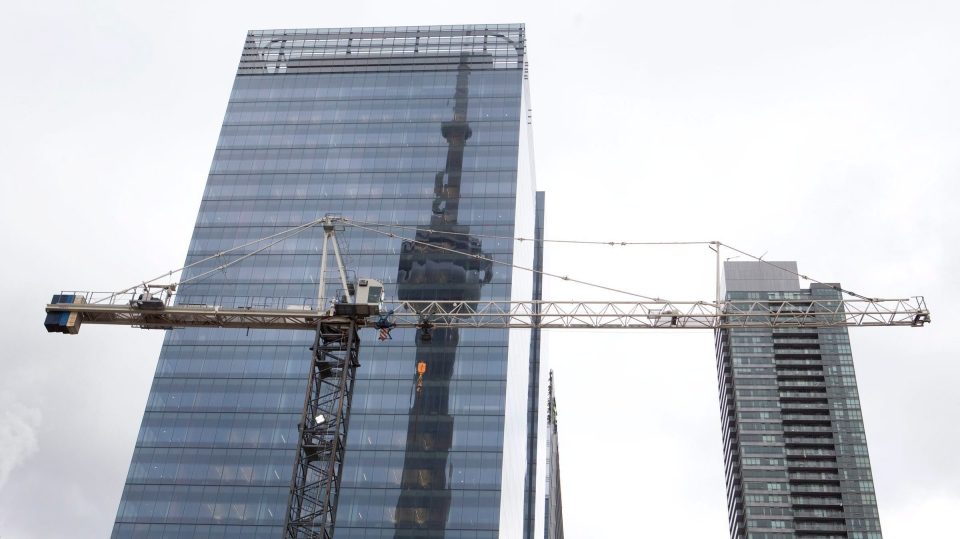The CN tower is reflected in a high rise building behind a construction crane in downtown Toronto on Saturday, February 4, 2012. (Pawel Dwulit/The Canadian Press)