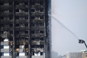 Firefighters spray water onto the 24-storey apartment block in west London. (Victoria Jones/PA via AP)