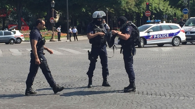 Car rams police van on Champs-Elysees, armed suspect dead